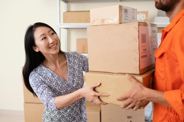Giovane donna sorridente che passa le scatole di consegna al corriere