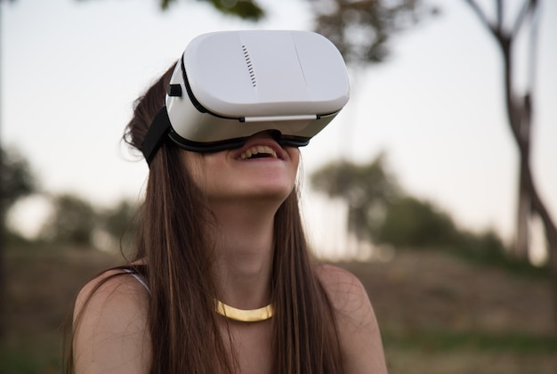 Smiling young woman having fun while using glasses of virtual reality in park.