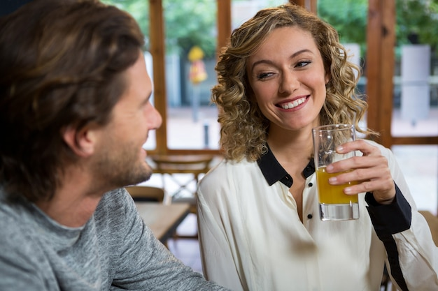 Smiling young woman having juice while looking at man in coffee shop