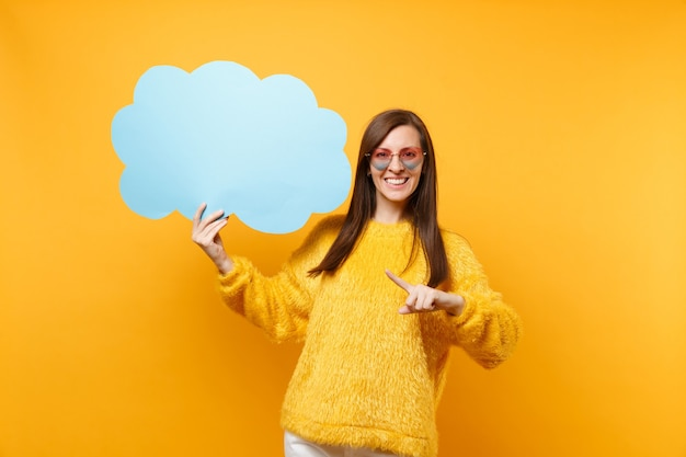 Smiling young woman in heart eyeglasses pointing index finger on empty blank blue say cloud, speech bubble isolated on yellow background. people sincere emotions, lifestyle concept. advertising area.