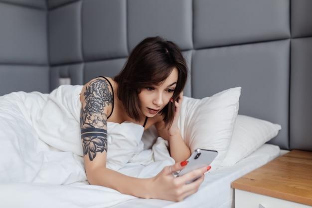 Усмехаясь молодая женщина держит smartphone лежа без сна в кровати в утре