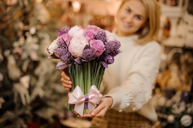 녹색 줄기와 부드러운 분홍색과 보라색 꽃의 꽃다발을 들고 웃는 젊은 여자
