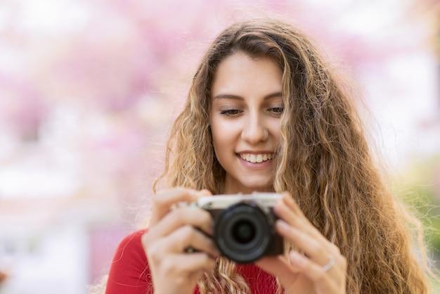 カメラを持って笑顔の若い女性