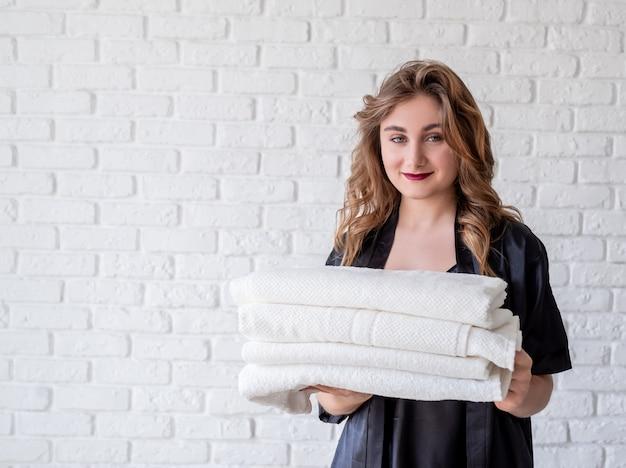 白いレンガの壁にタオルの山を保持している若い女性を笑顔