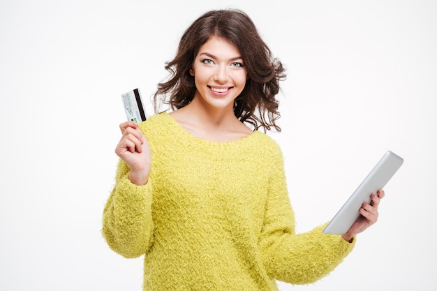 Улыбающаяся молодая женщина, держащая банковскую карту и планшетный компьютер, изолированные на белом фоне