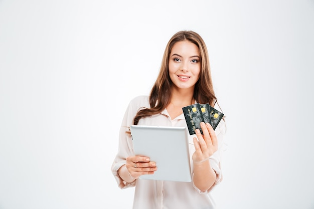 Smiling young woman holding bank card and tablet computer isolated on a white wall