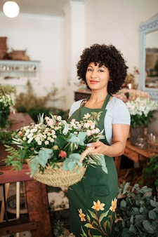 Smiling young woman holding basket of flowers in floral shop