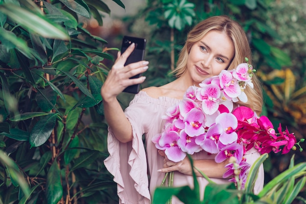 Smiling young woman holding beautiful orchid branches in hand taking selfie on smart phone
