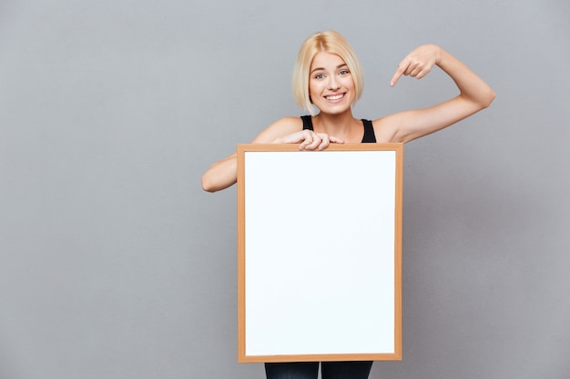 Улыбающаяся молодая женщина держит пустую белую доску и указывает на нее над серой стеной