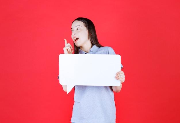 Sorridente giovane donna che tiene la tavola e punta il dito in su