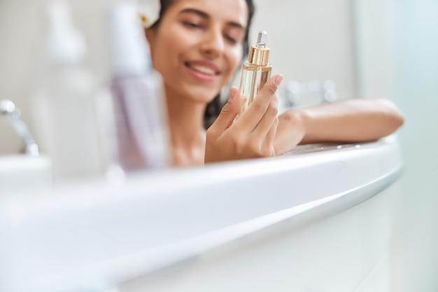 목욕하는 동안 얼굴 혈청 병을 들고 웃는 젊은 여자