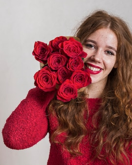 Smiling young woman holding a bouquet of roses