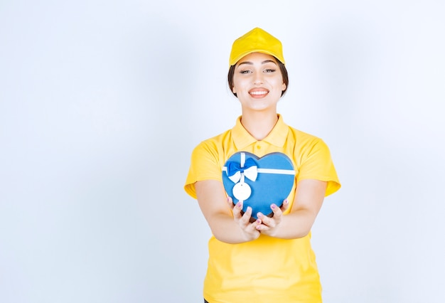 Sorridente giovane donna in possesso di una scatola a forma di cuore su un muro bianco