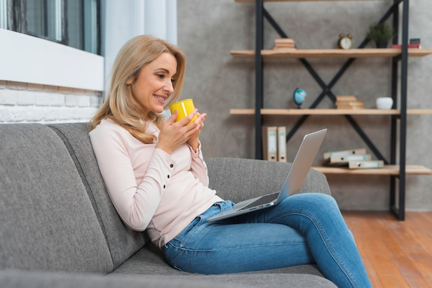 Smiling young woman holding cup of coffee looking at laptop