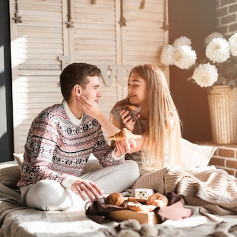 Smiling young woman holding cupcake loving her boyfriend holding croissant