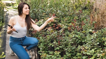 Smiling young woman holding digital tablet in hand pointing at plants in the garden