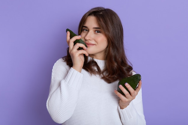 ライラックの壁に隔離された手に新鮮な熟した緑のアボカドの果実を持って、エキゾチックな果実の香り、白いセーターを着て、優しくて喜びを表現する笑顔の若い女性。