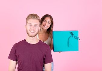 Smiling young woman holding gift box standing behind smiling man against pink backdrop