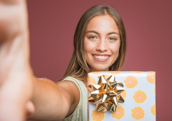 Smiling young woman holding gift box taking selfie