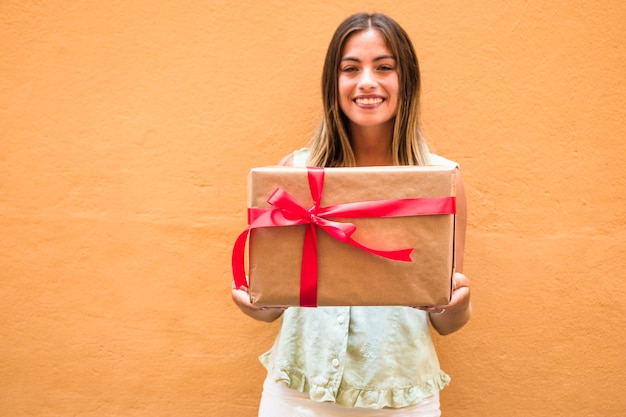 Smiling young woman holding gift box tied with red ribbon