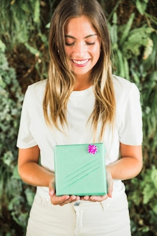 Smiling young woman holding green gift box
