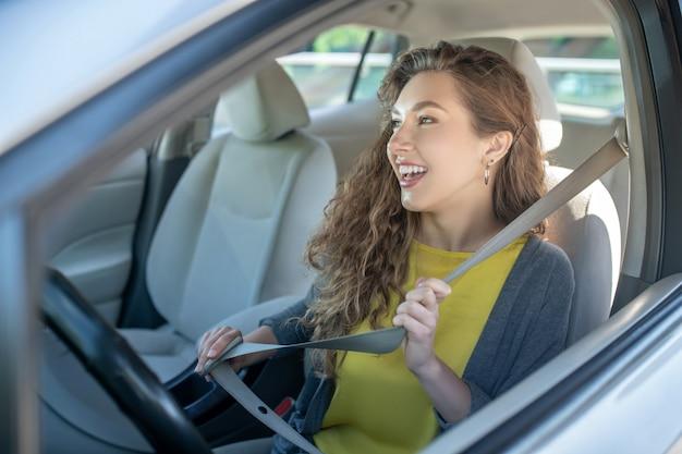 シートベルトに手を繋いでいる笑顔の若い女性