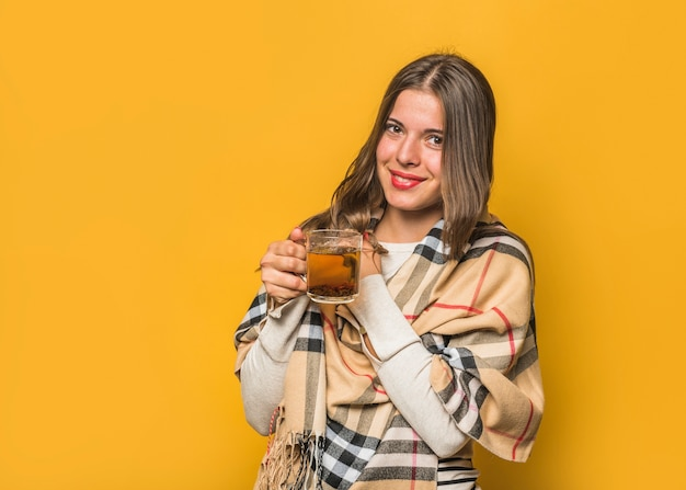 Smiling young woman holding herbal tea cup in the hands against yellow background