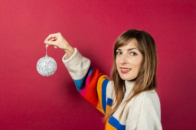 ブルゴーニュの背景に装飾的な銀のボールを手に持って笑顔の若い女性。休日、rozhdestovo、新年のコンセプトの準備。