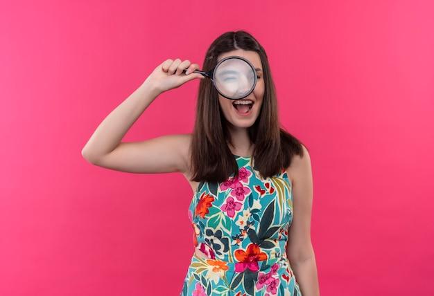 Giovane donna sorridente che tiene il vetro della lente di ingrandimento e guardando attraverso di essa sul muro rosa isolato