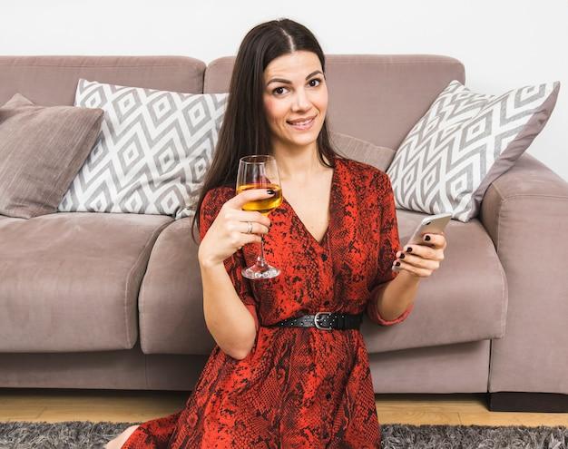 携帯電話とワイングラスを手に持ってソファのそばに座っている若い女性の笑みを浮かべてください。