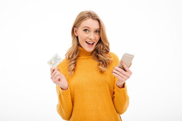 Smiling young woman holding mobile phone and credit card.