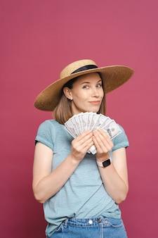 Sorridente giovane donna che tiene soldi sul muro rosa