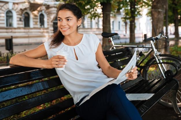 Улыбающаяся молодая женщина, держащая газету, сидя на скамейке с чашкой кофе