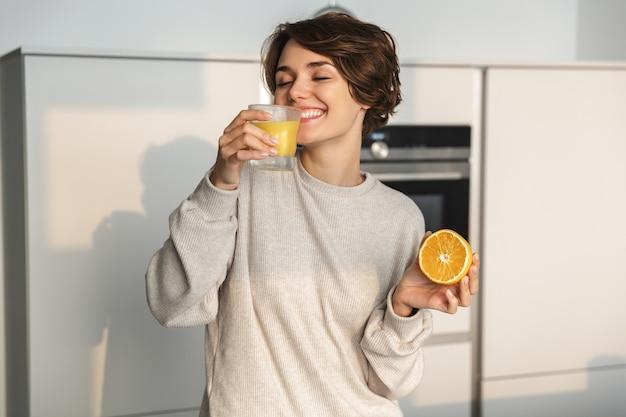 Улыбающаяся молодая женщина, держащая апельсиновый сок и апельсиновые фрукты, стоя на кухне