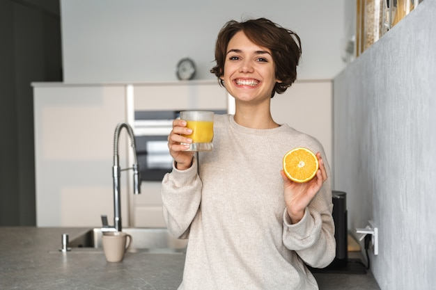 Smiling young woman holding orange juice and orange fruit while standing at the kitchen