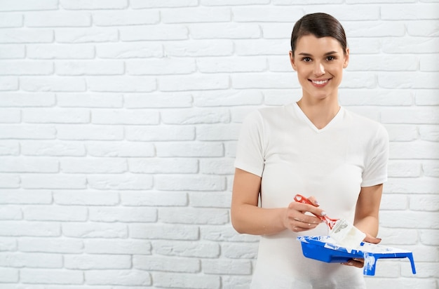 Smiling young woman holding paint and brush