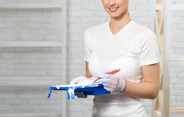 Smiling young woman holding paint