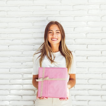 Smiling young woman holding pink gift box
