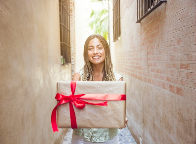 Smiling young woman holding present