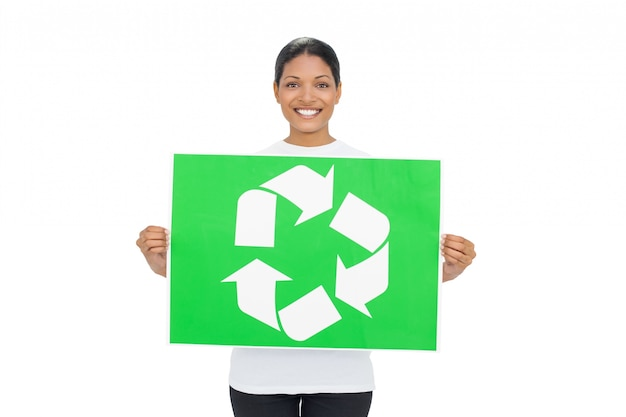 Smiling young woman holding recycling sign