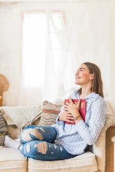Giovane donna sorridente che tiene libro rosso
