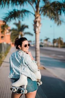 Улыбается молодая женщина, держащая роликовые коньки на плече, глядя через плечо