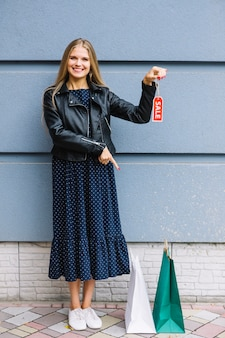 Smiling young woman holding sale tag in hand pointing finger at shopping bags