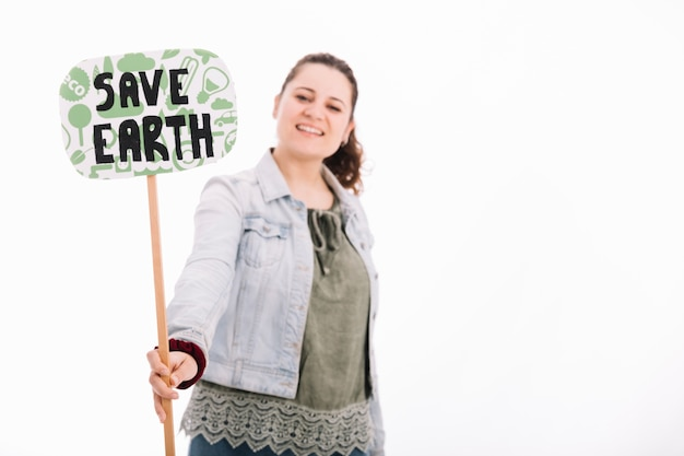 Smiling young woman holding save earth placard against white background