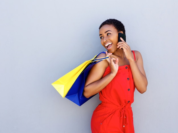 Smiling young woman holding shopping bags talking on cell phone