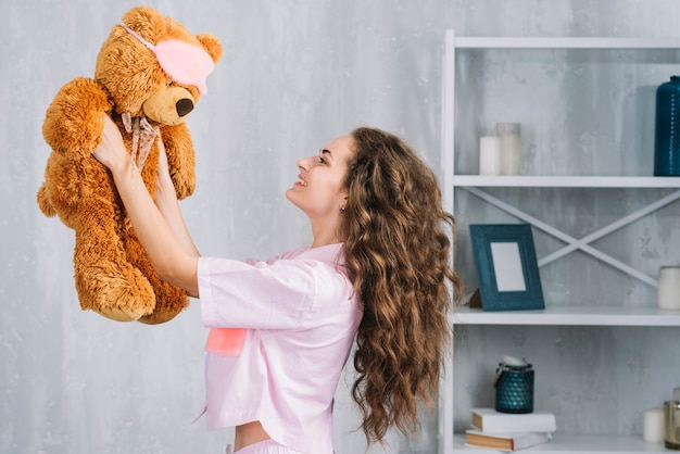 Smiling young woman holding soft toy