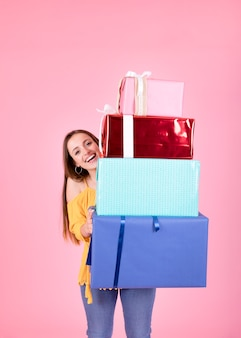 Smiling young woman holding stack of gift boxes standing against pink background