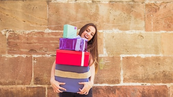 Smiling young woman holding stacked gifts against weathered wall