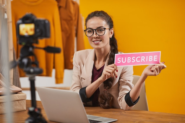 Smiling young woman holding subscribe button