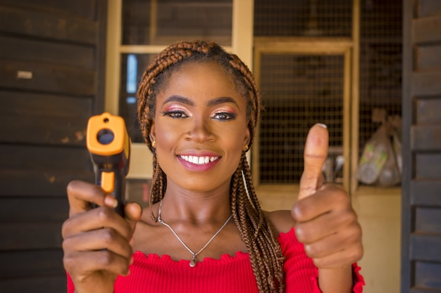 Smiling young woman holding a thermal gun scanner with thumbs up